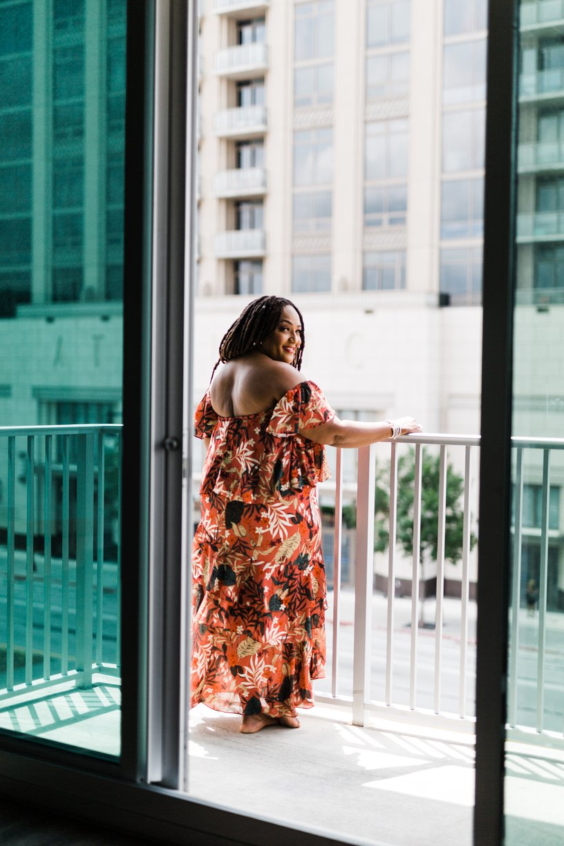 Blogger Nikki Free standing on a balcony looking over shoulder