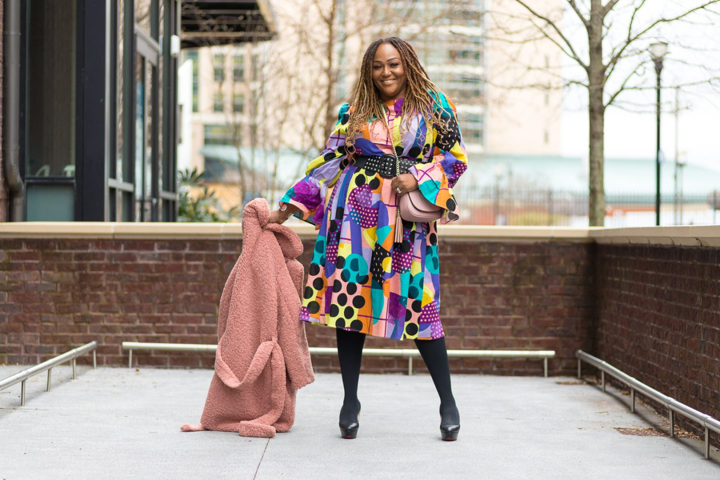 Nikki Free wearing colorful print dress from SHEIN holding Teddy Coat