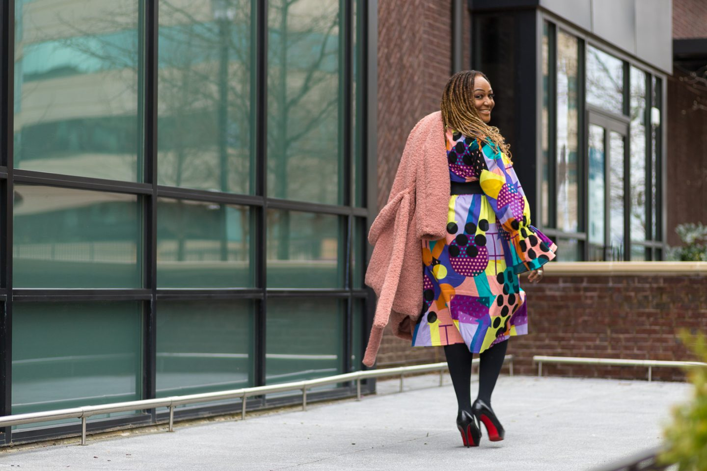 Nikki Free wearing colorful print dress from SHEIN with Teddy Coat over shoulder