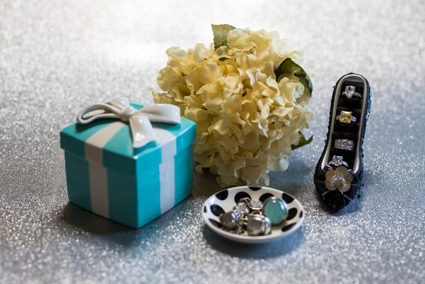 Photo of diamond rings in a dish, a ceramic Tiffany box and flower