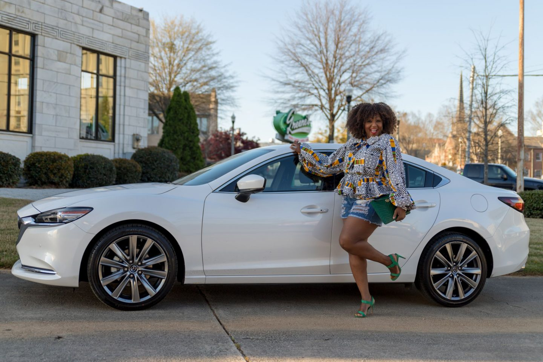 Influencer Nikki Free kicks up her leg while standing beside Mazda6 Signature