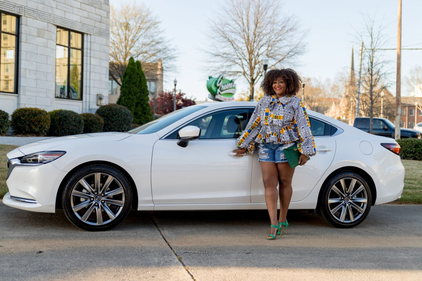 Plus size influencer Nikki Free stands beside a white Mazda6 Signature