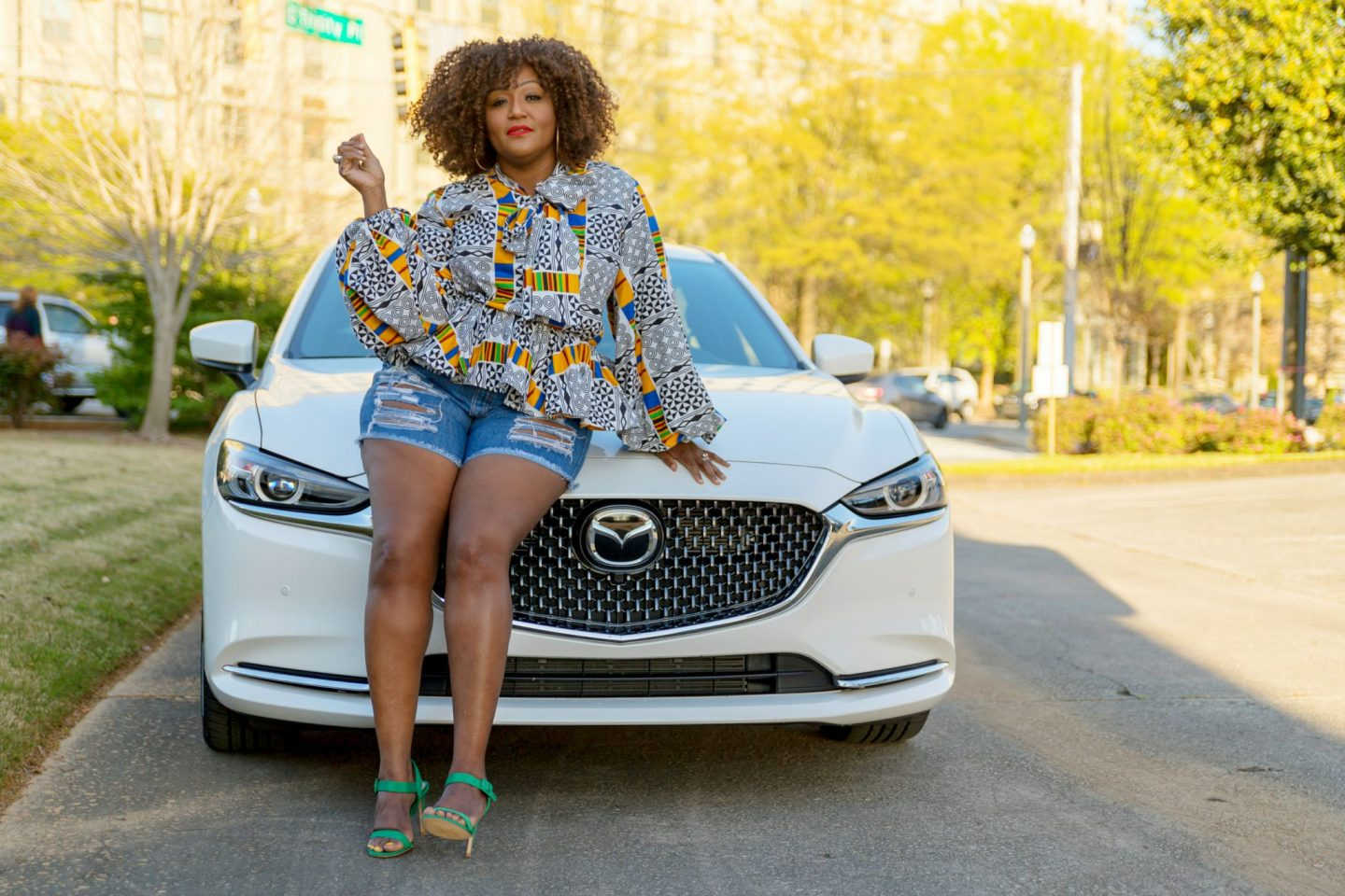 Influencer Nikki Free sits on the hood of the Mazda6 Signature