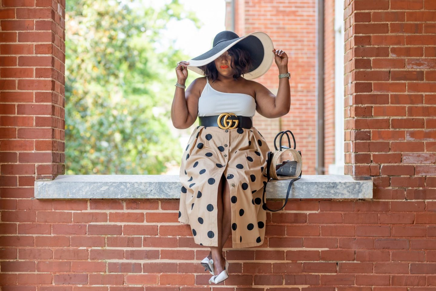 Blogger Nikki Free wearing khaki skirt with black polka dot print sitting on a brick wall