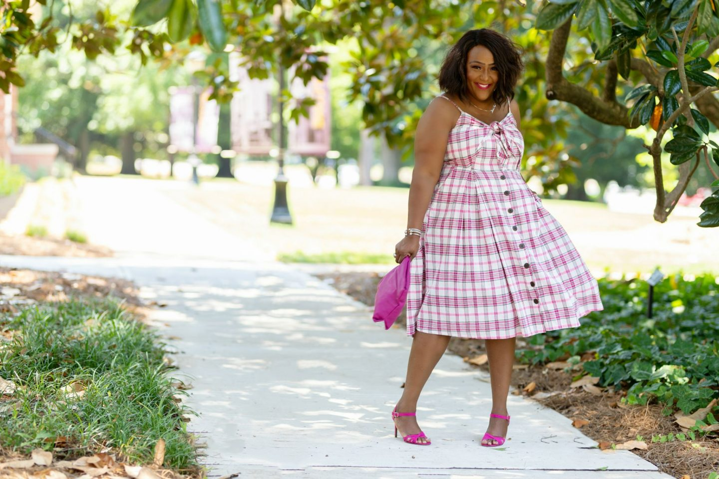 Influencer Nikki Free posing in a plaid sundress standing under a magnolia tree