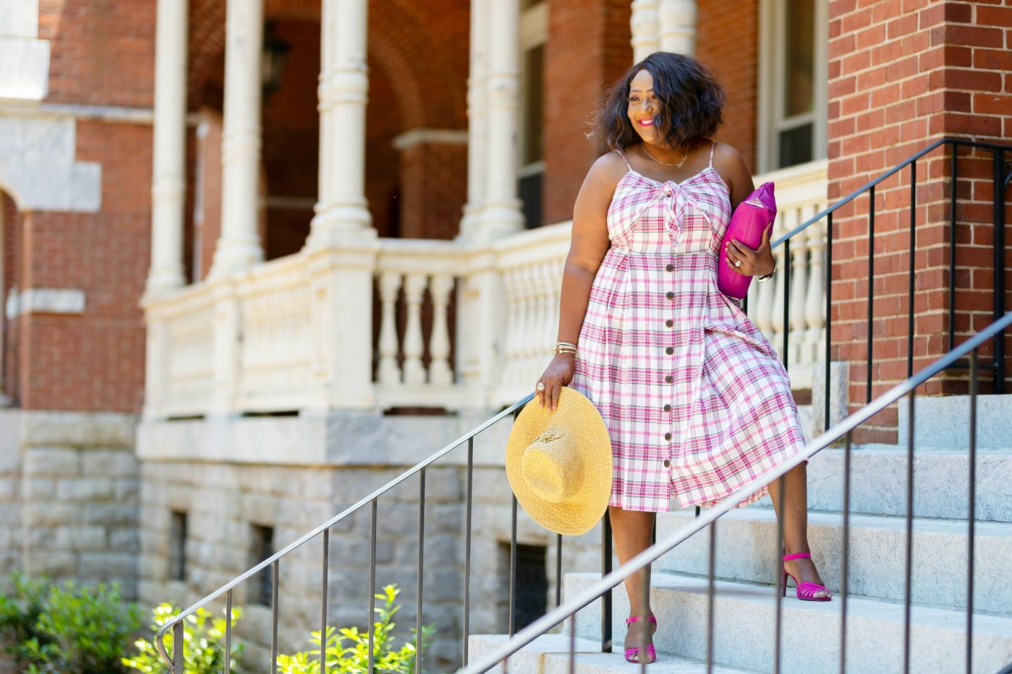 Influencer Nikki Free posing in a plaid sundress standing on stairs holding pink clutch and straw sunhat