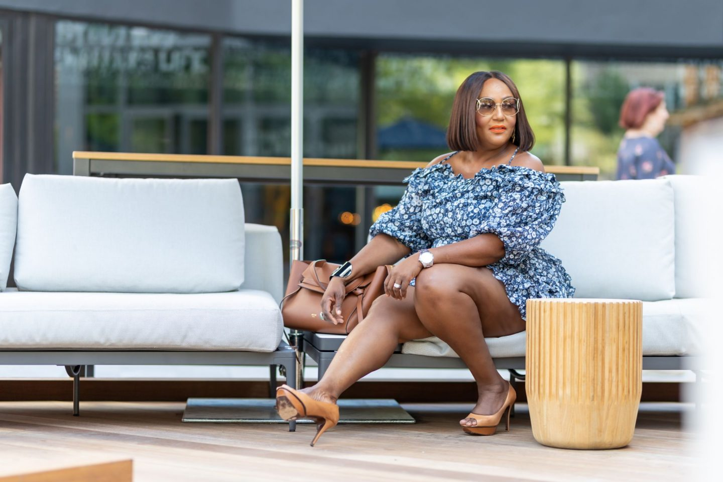 Influencer NikkiFree sitting on outdoor furniture wearing short skirt with legs exposed