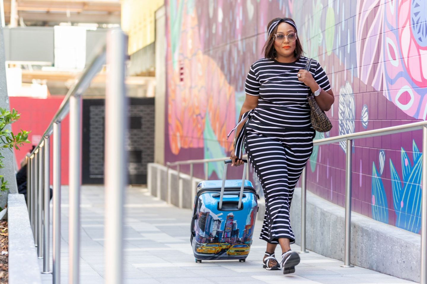Influencer Nikki Free in black and white stripe coordinates pulling luggage