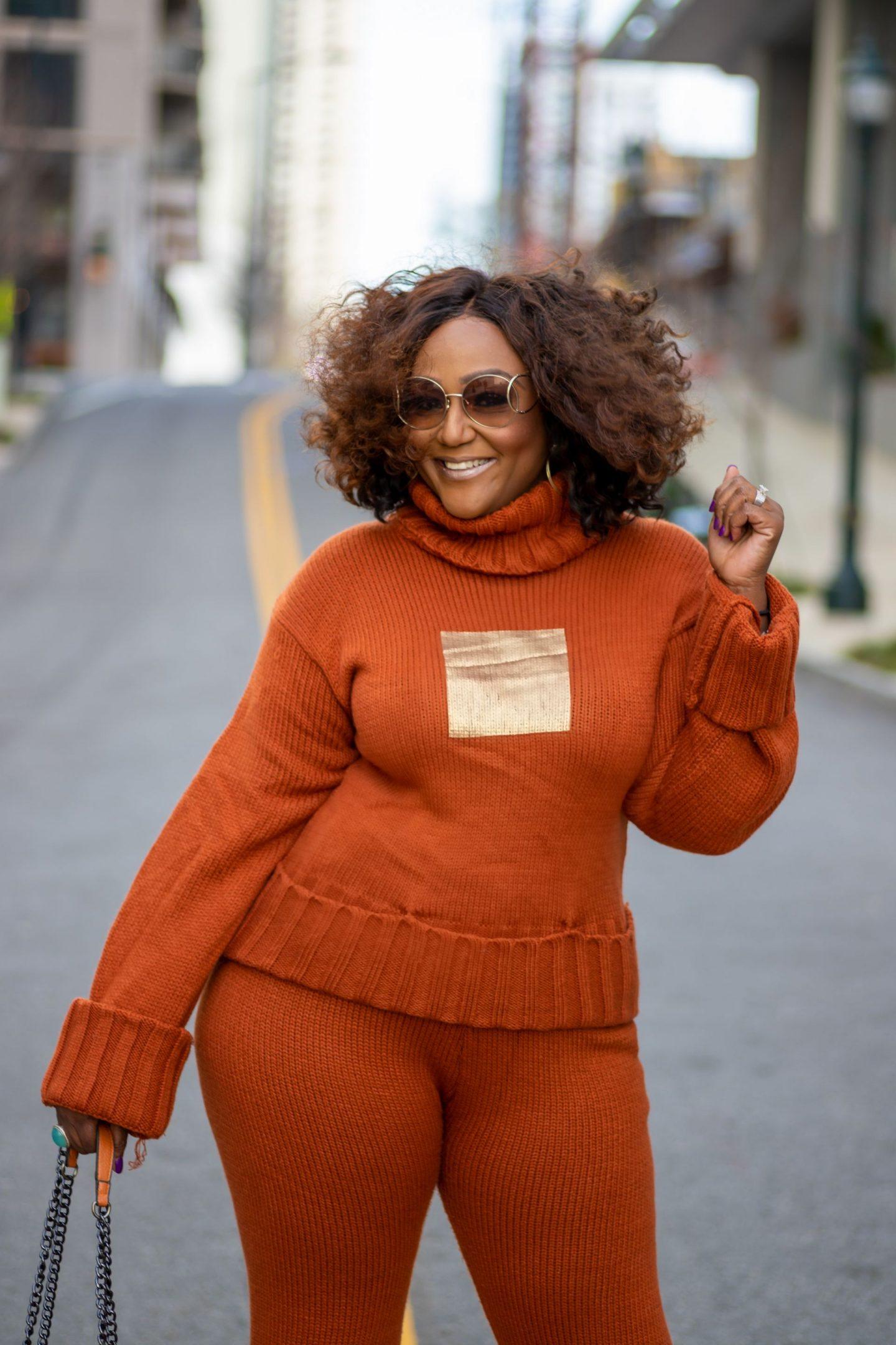 Black woman standing in street wearing orange sweater