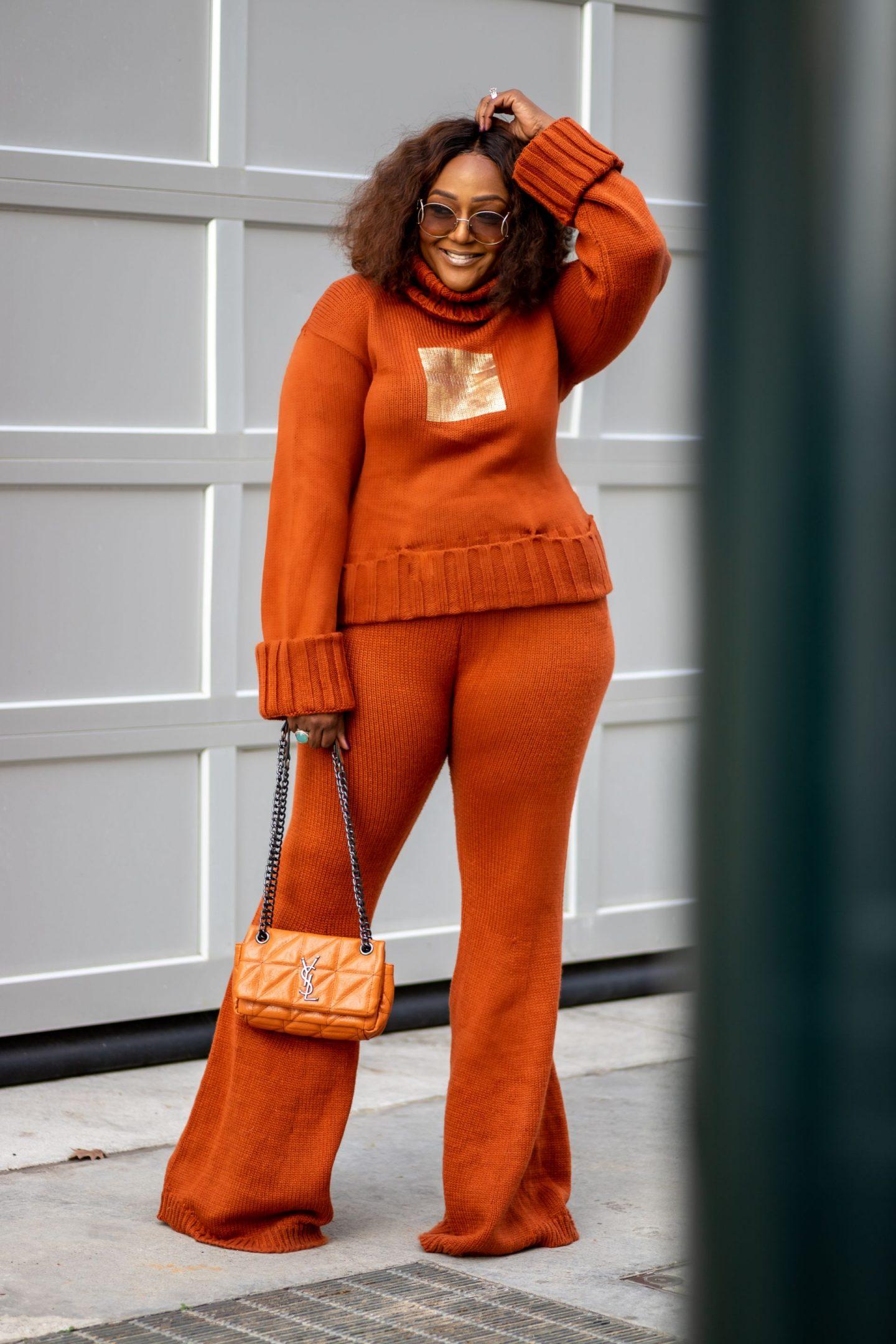 Blogger Nikki Free wearing orange sweater and pants