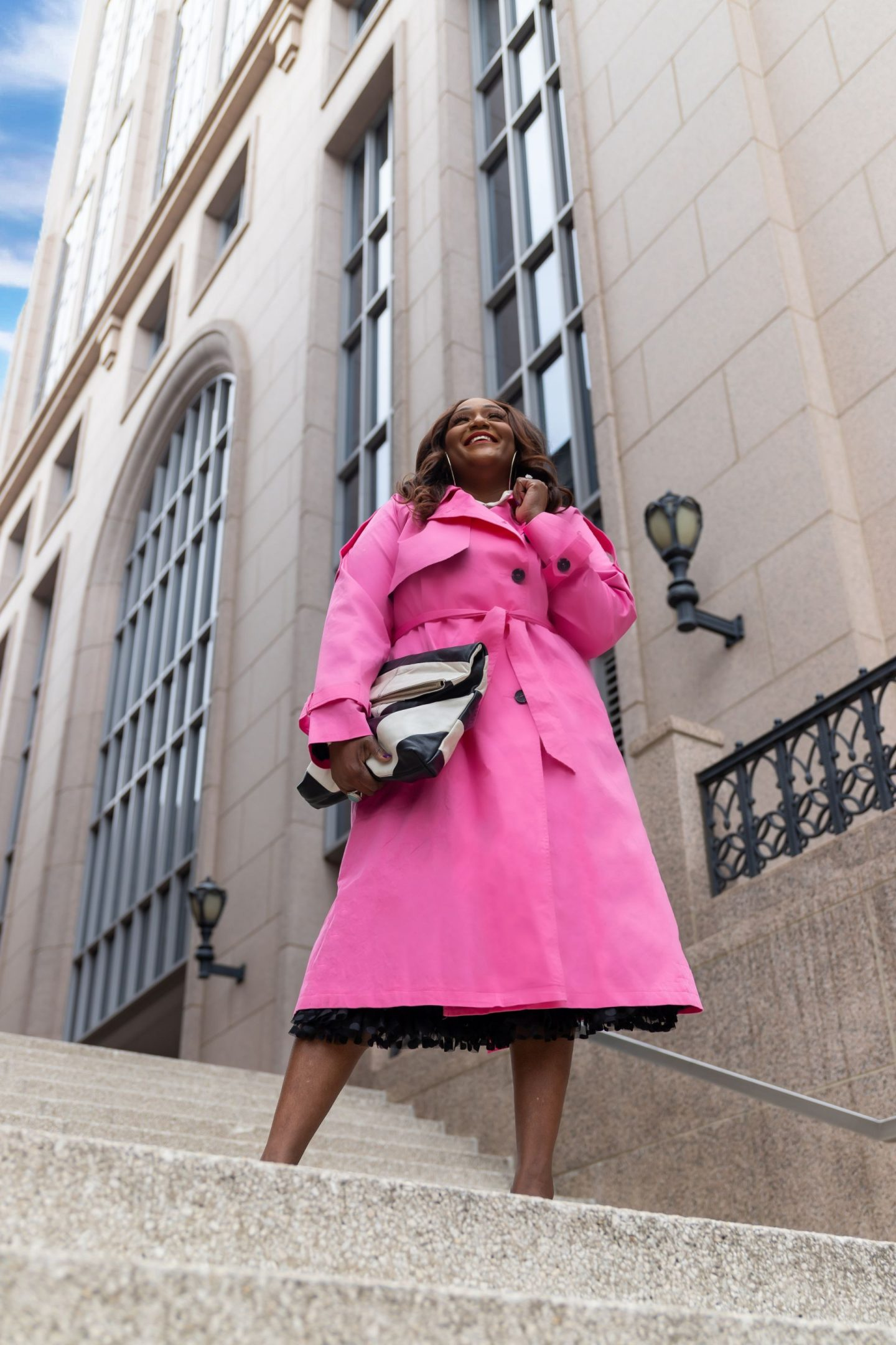 Influencer Nikki Free standing on stairs wearing a pink trench coat holding black and white clutch bag