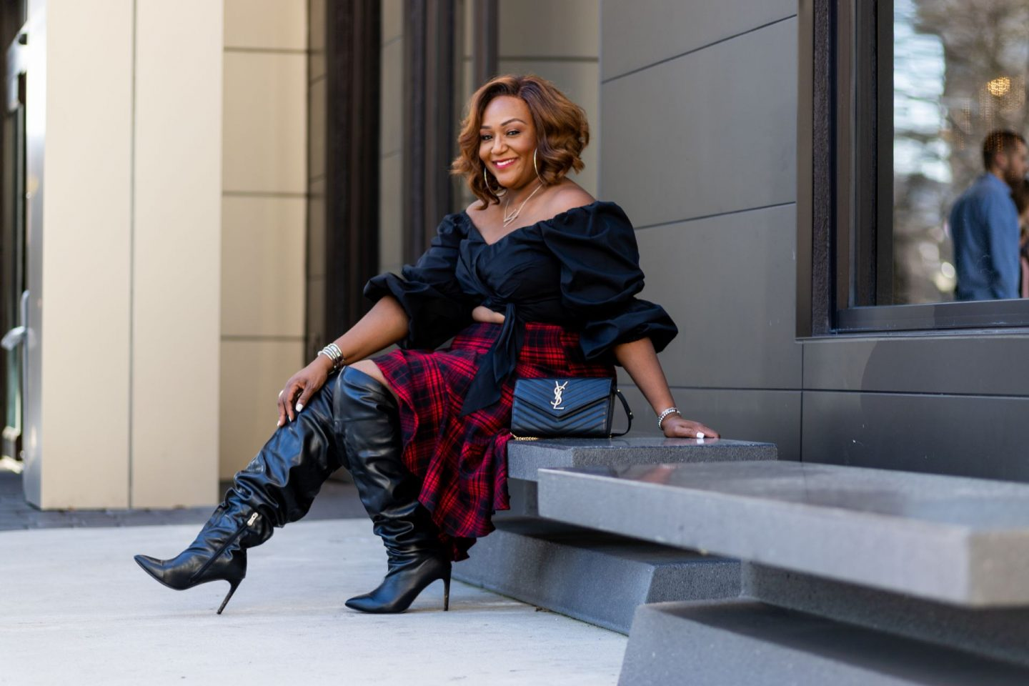 Black woman sitting on bench wearing over the knee boots