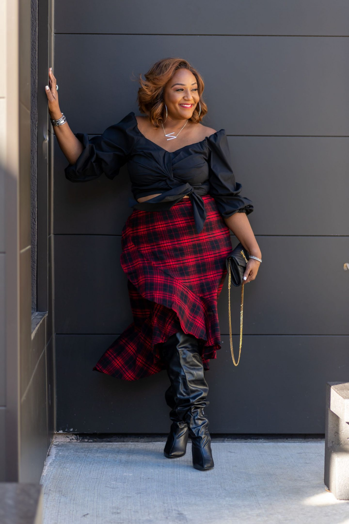 Black woman leaning on wall wearing over the knee boots