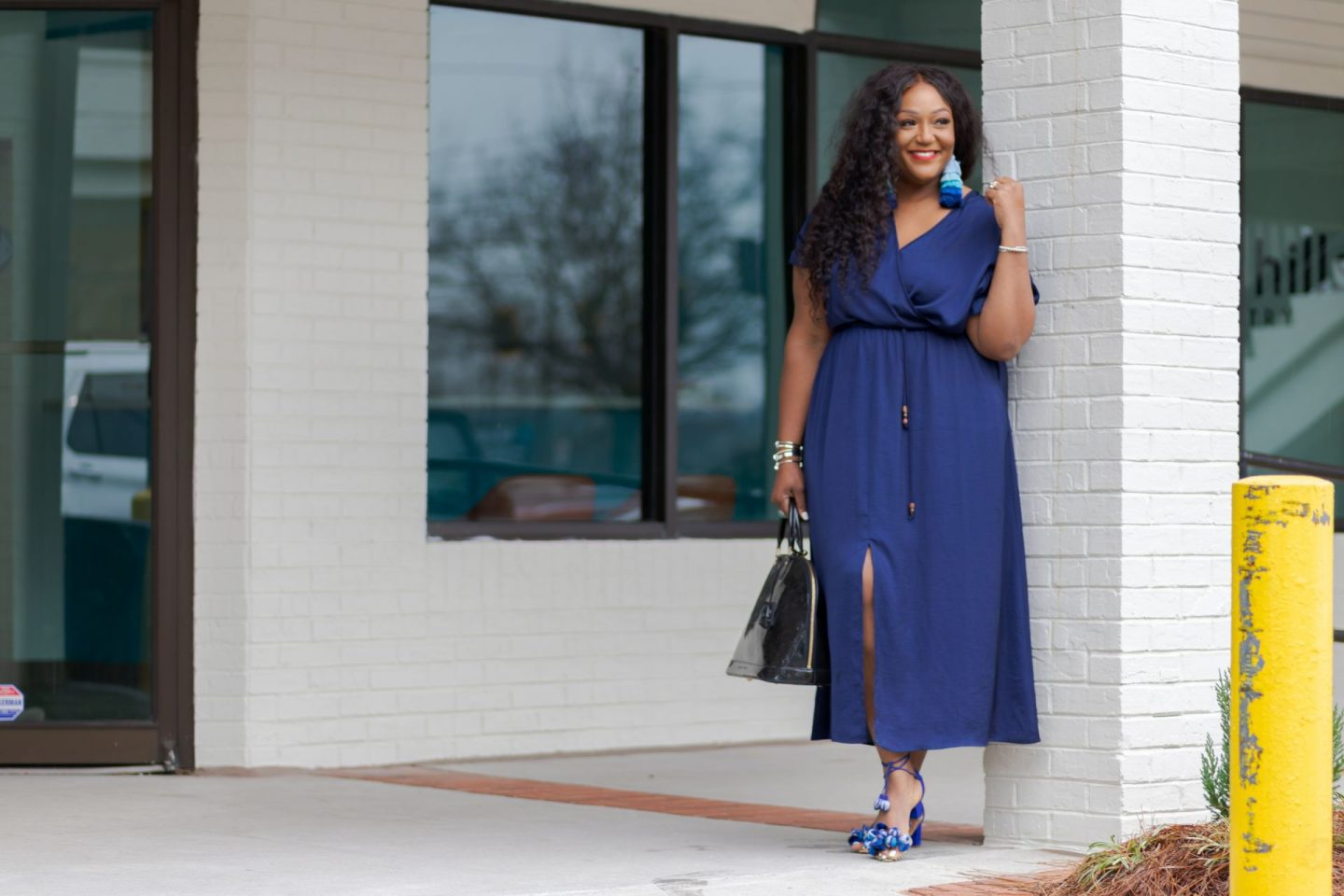 Black Woman wearing blue dress leaning on wall