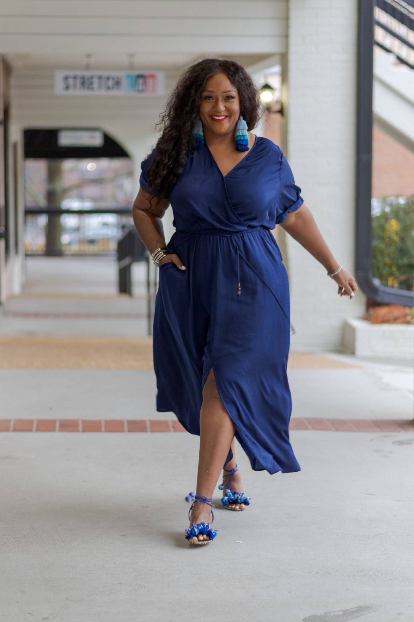 Influencer Nikki Free walking down sidewalk in blue dress