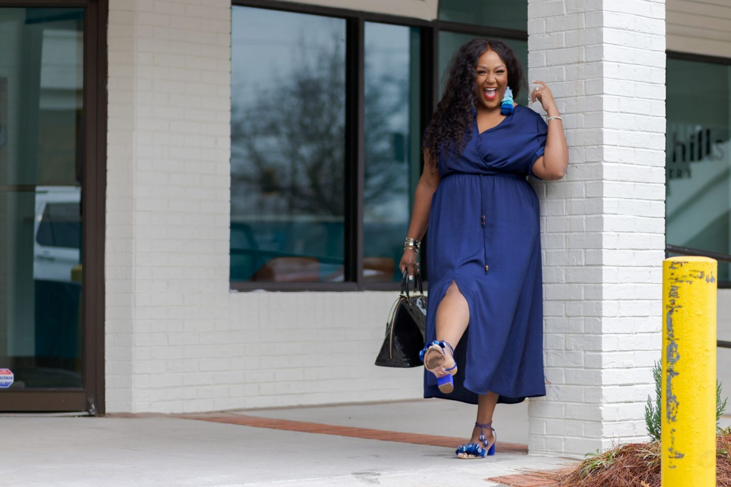 Black Woman in blue dress kicking up her leg
