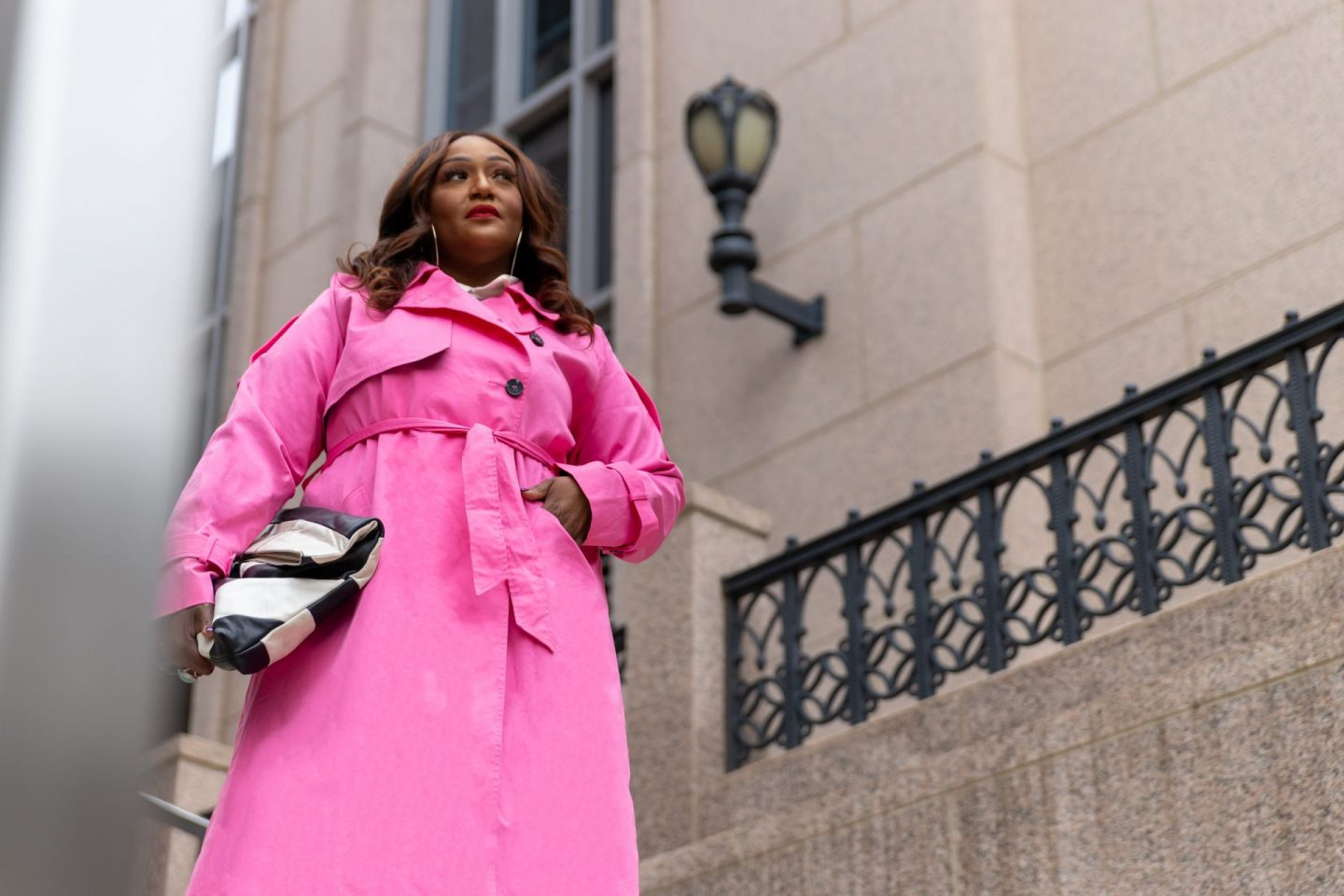 Influencer Nikki Free standing on stairs wearing a pink trench coat