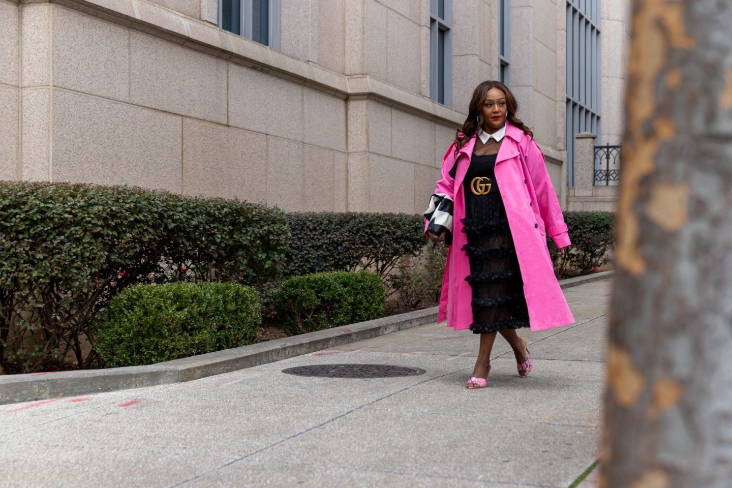 Influencer Nikki Free walking on sidewalk wearing a pink trench coat