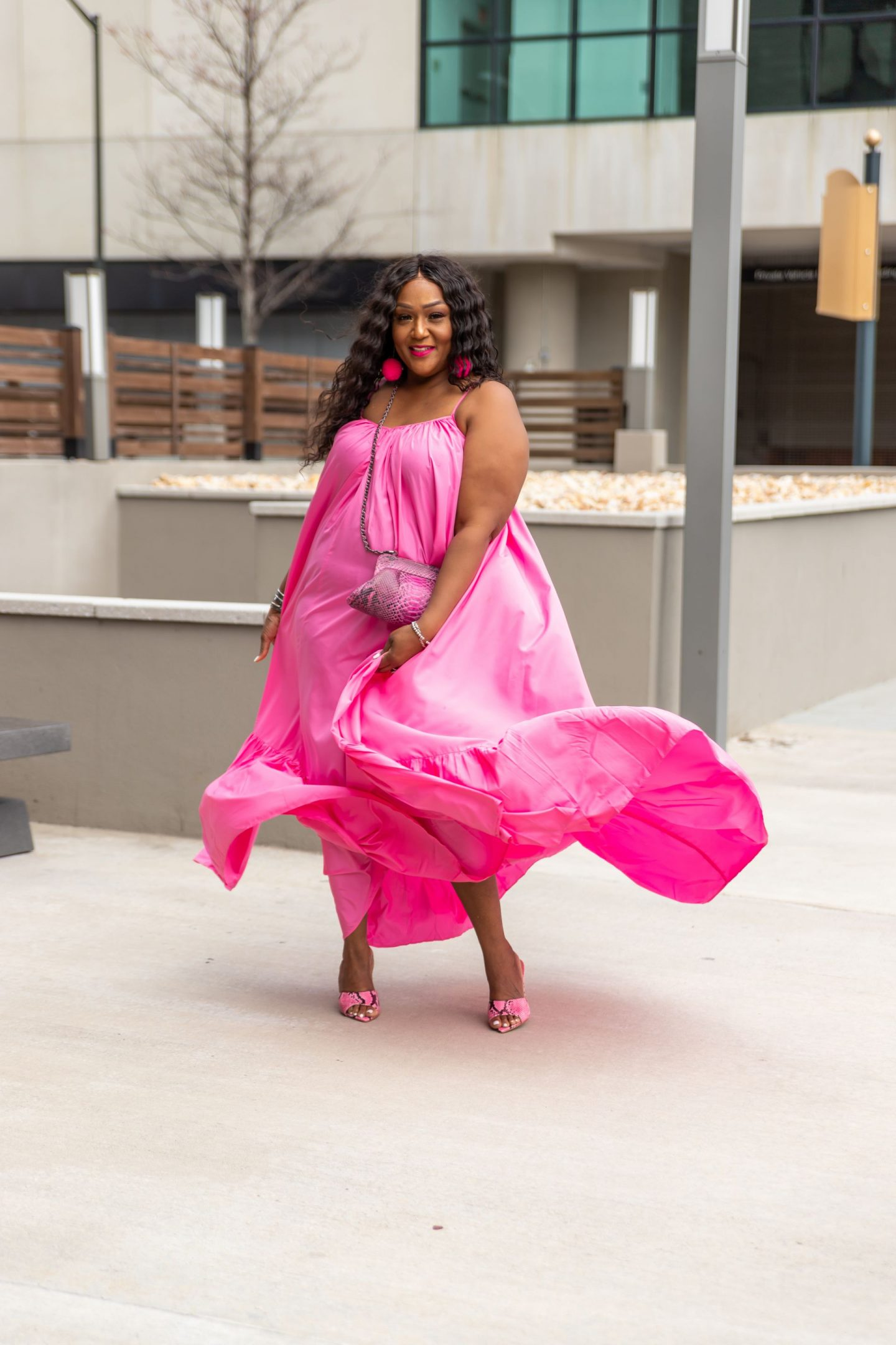 Blogger Nikki Free twirling in flowing pink dress