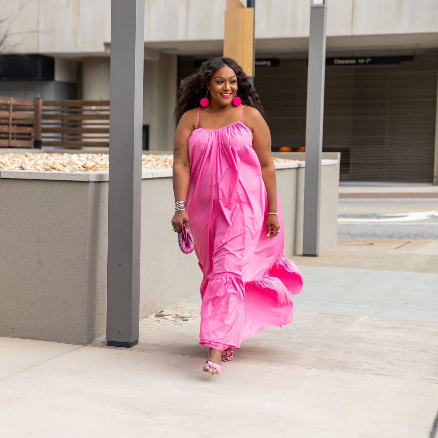 Blogger Nikki Free walking in flowing pink maxi sundress