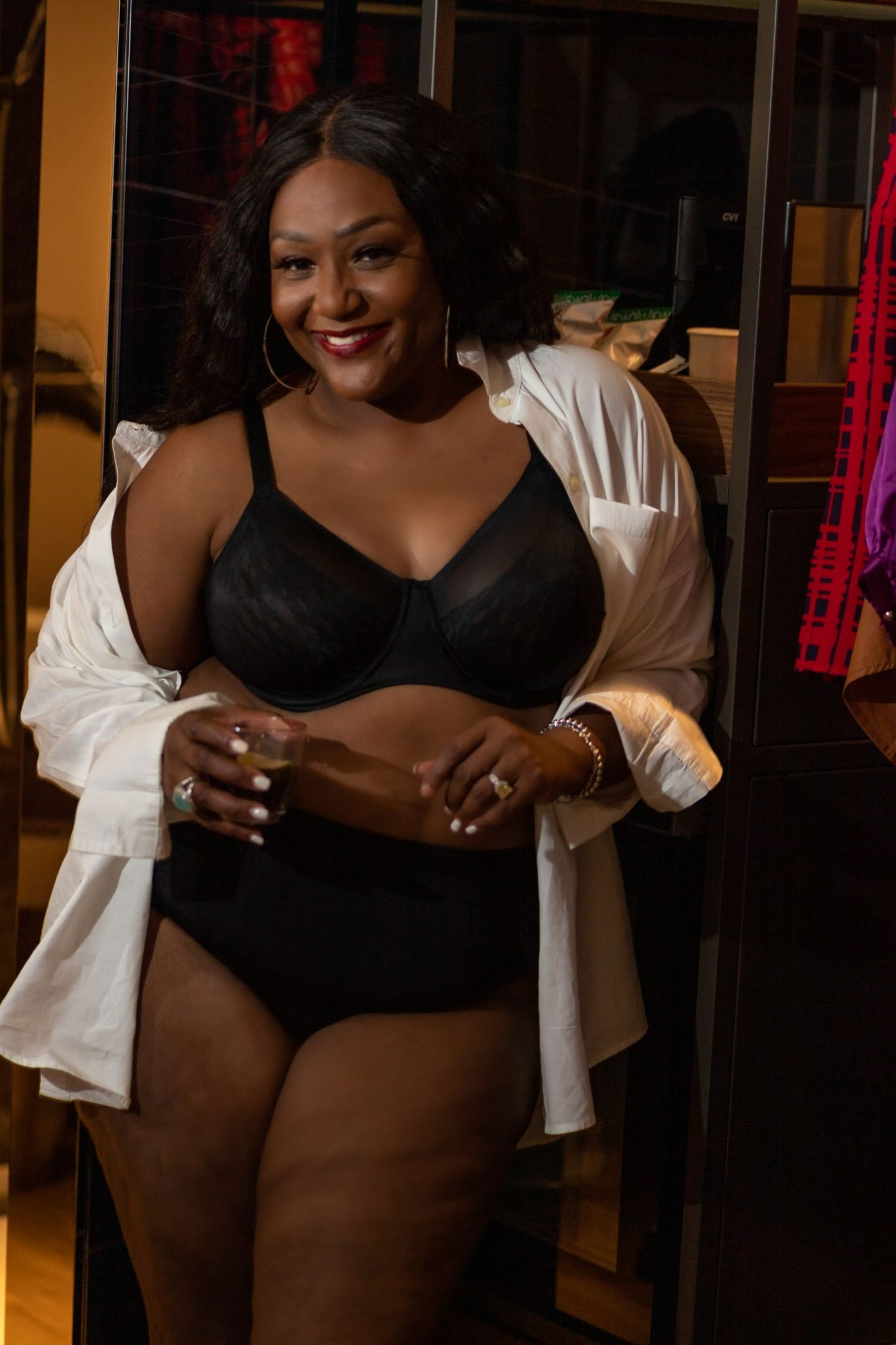 Black blogger sipping a cocktail wearing undergarments